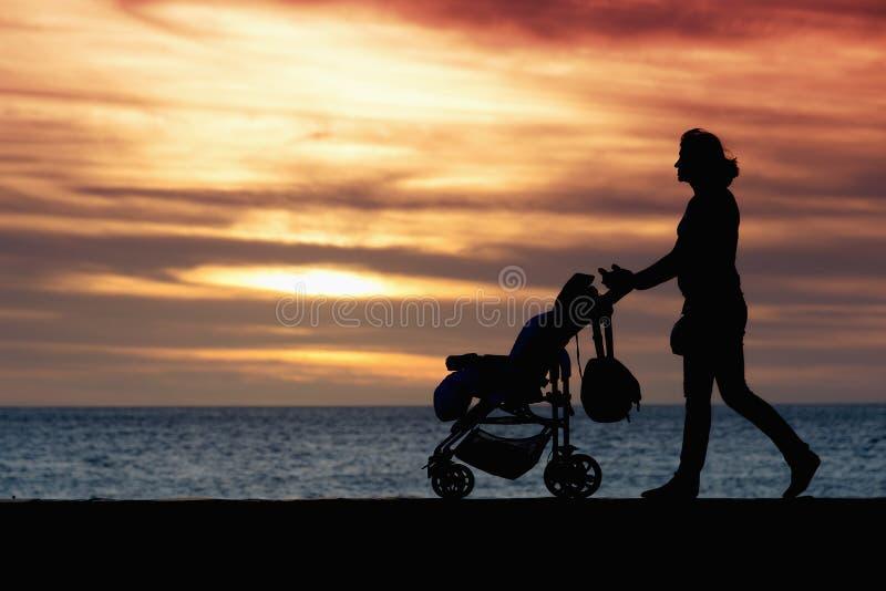 Мать силуэта вытягивая детскую сидячую коляску стоковая фотография rf