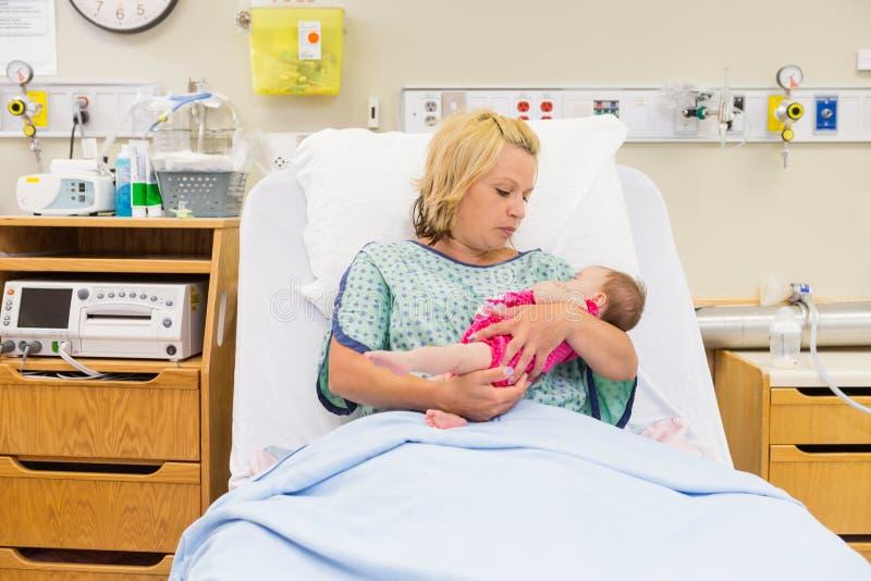 Мать смотря Newborn ребёнок пока сидящ стоковое изображение rf