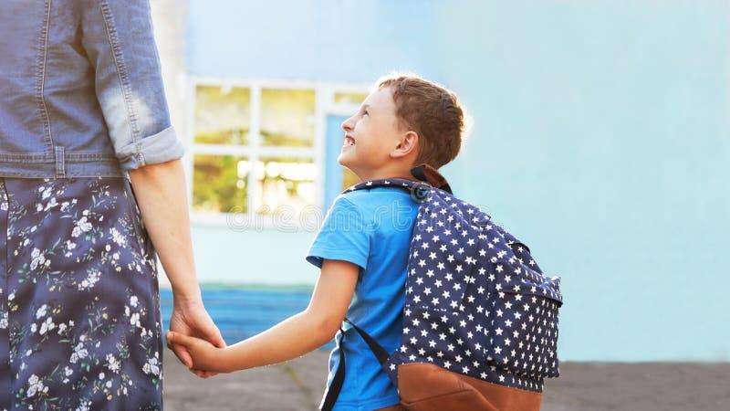 Мать сопровождает ребенка в школу мама ободряет студента сопровождая его в школу заботя мать смотрит нежно на ей стоковые фото