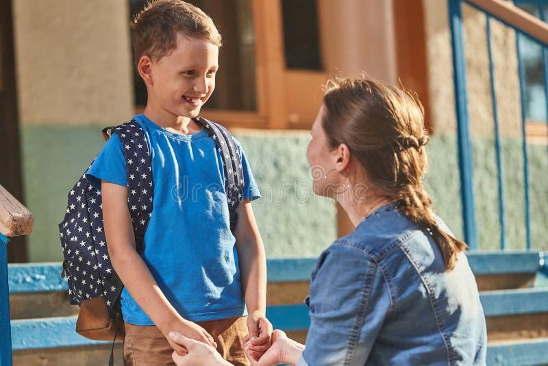 Мать сопровождает ребенка в школу мама призывает ученика сопровождать его в школу заботливая мать нежно смотрит на нее стоковое фото rf