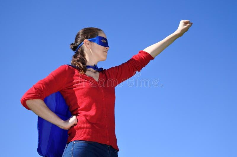 Мать супергероя против предпосылки голубого неба стоковые фотографии rf
