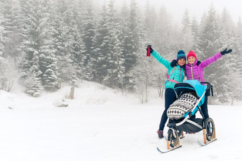 Мать с детской сидячей коляской наслаждаясь лесом зимы с женскими другом или партнером, временем семьи Женщина пешего туризма или стоковое изображение rf