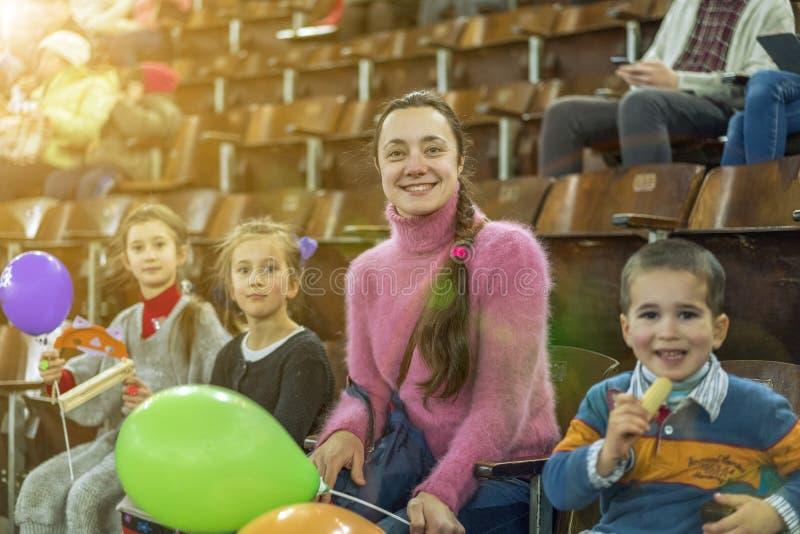Мать с 3 детьми сидит на концерте Дети с раздувными шариками в цирке 2 сестры и брат на t стоковое изображение