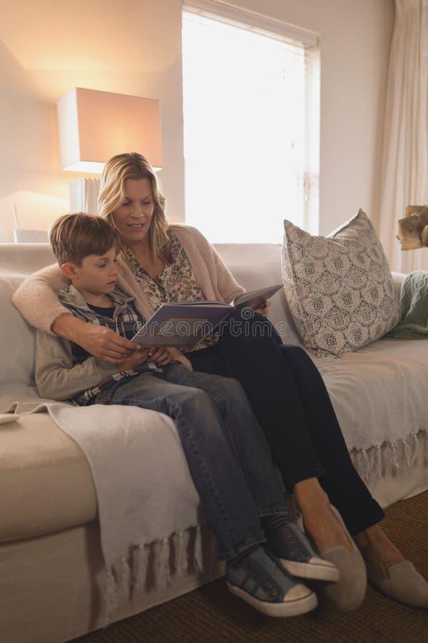 Мать с ее книгой рассказа чтения сына в живя комнате стоковая фотография rf
