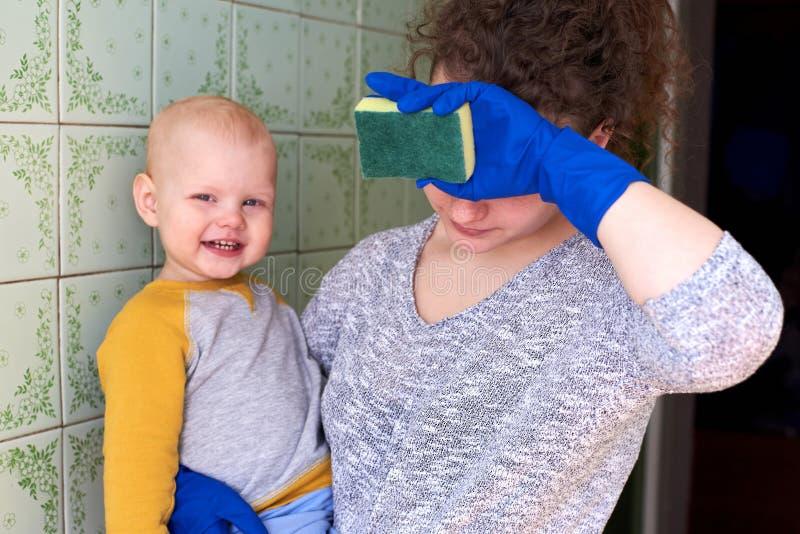 Мать с ее маленьким сыном убирает дом Концепция совмещения домашней работы и поднимать ребенка стоковая фотография
