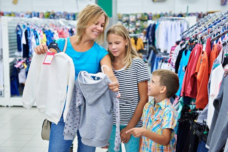 Мать с детьми в магазине одежды стоковые фотографии rf