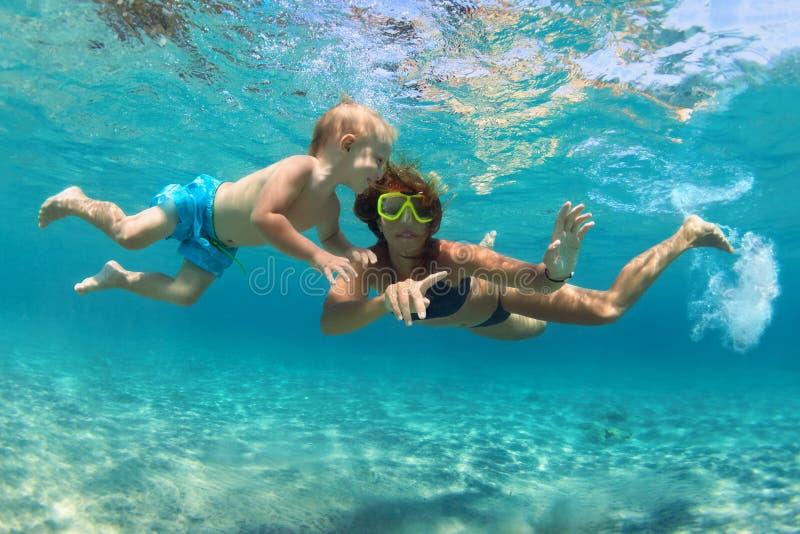 Мать с заплывом ребенка подводным с потехой в море стоковые изображения rf