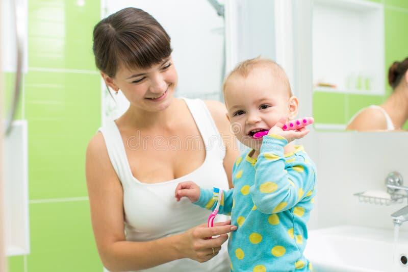 Мать с зубами младенца чистя щеткой стоковое изображение rf