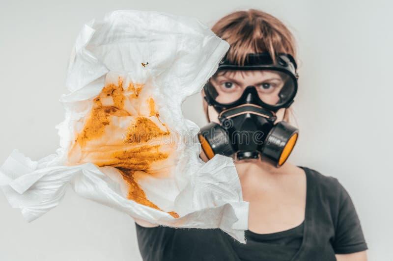 Мать с маской противогаза изменяя вонючую пеленку стоковое изображение