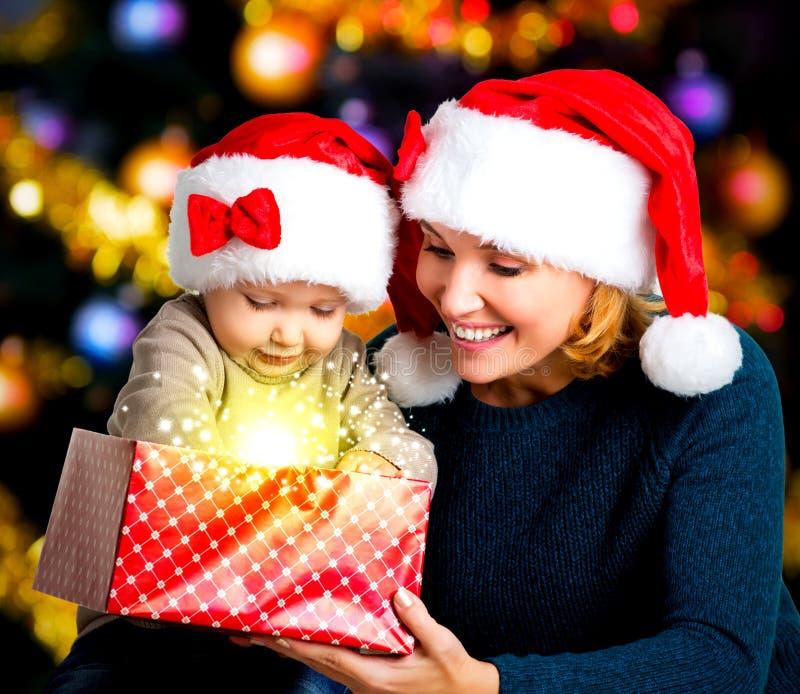 Мать с маленьким ребенком раскрывает коробку с подарками на рождестве стоковые фотографии rf