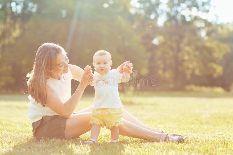 Мать с ребенком играя на траве на заходе солнца стоковая фотография rf