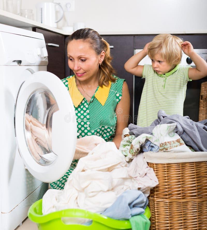 Мать с ребенком около стиральной машины стоковое фото