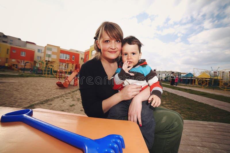 Мать с сыном на спортивной площадке стоковые изображения