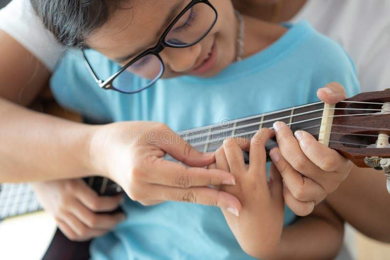 мать учила дочь играть на акустической классической гитаре джаза, и легкая песня слушания выберите фокус мелкий стоковое фото rf