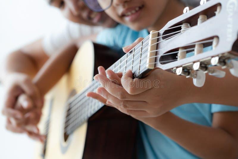 мать учила дочь играть на акустической классической гитаре джаза, и легкая песня слушания выберите фокус мелкий стоковая фотография rf