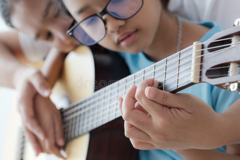 мать учила дочь играть на акустической классической гитаре джаза, и легкая песня слушания выберите фокус мелкий стоковое изображение rf