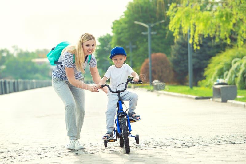 Мать учит его маленького сына для того чтобы ехать велосипед стоковое фото rf