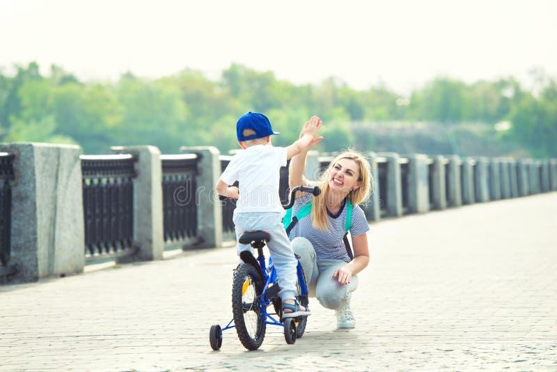 Мать учит его маленького сына для того чтобы ехать велосипед стоковое фото
