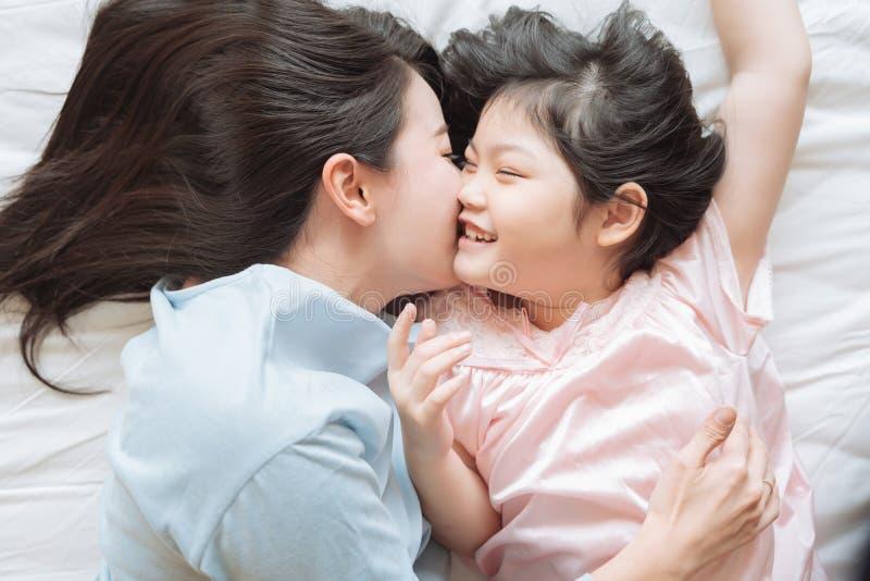 Мать целует ее щеку дочери и обнимающ в спальне Счастливая азиатская семья стоковые фото