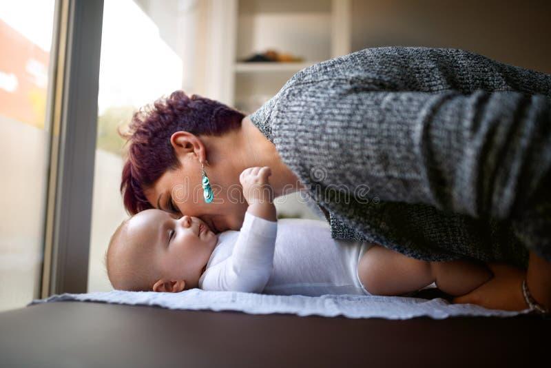 Мать целуя его сына стоковые изображения rf