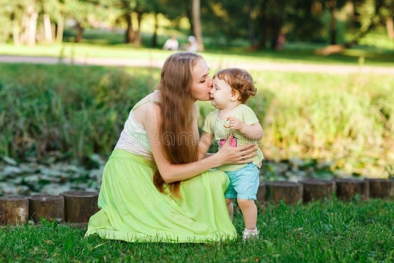Мать целует дочь в парке на зеленой лужайке стоковое фото