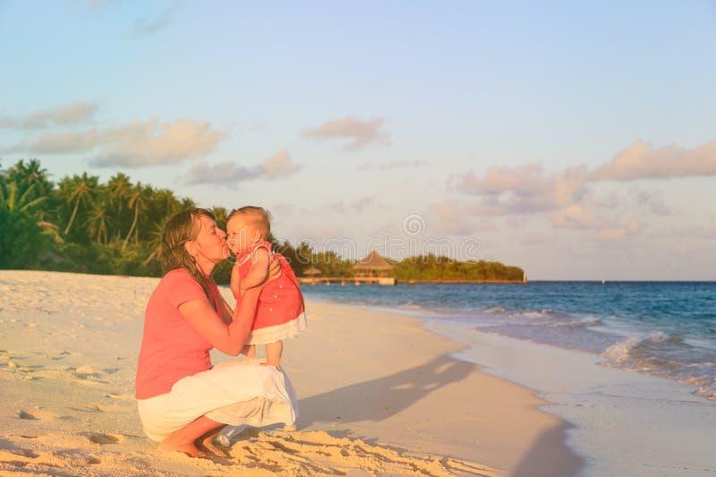 Мать целуя маленькую дочь на пляже захода солнца стоковая фотография rf