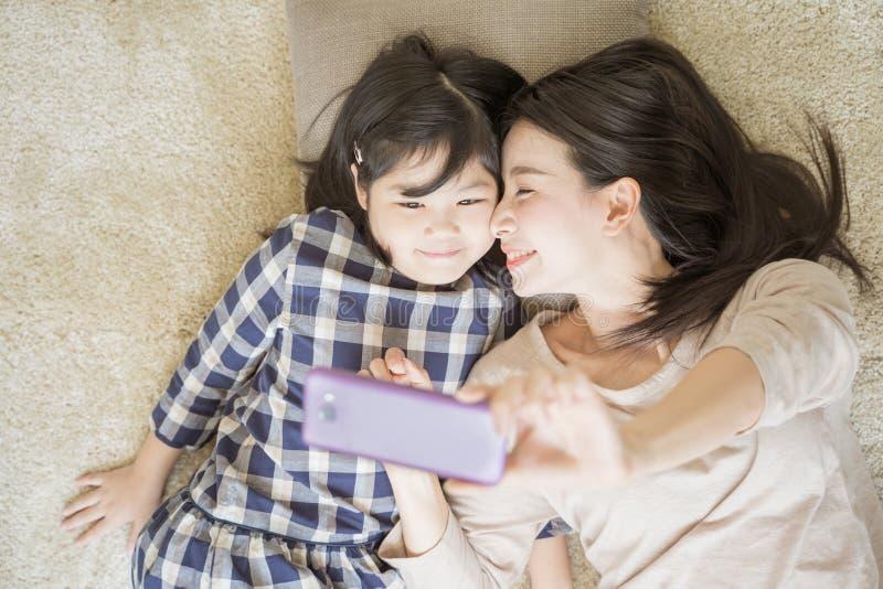 Мать selfie с ее маленькой дочерью используя умную камеру телефона пока целующ щеку дочери стоковое фото rf