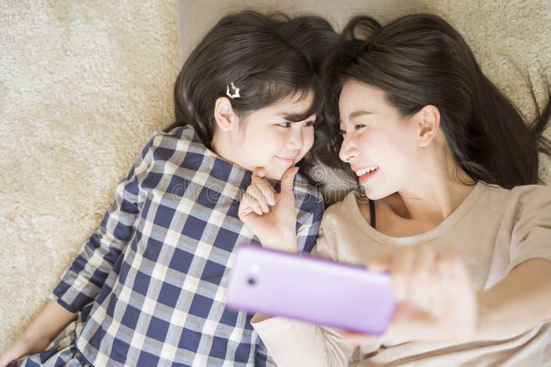 Мать selfie с ее маленькой дочерью используя умную камеру телефона пока визуальный контакт с дочерью Азиатская концепция семьи стоковая фотография rf