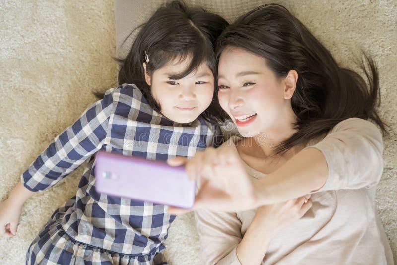 Мать selfie с ее маленькой дочерью используя умную камеру телефона с дочерью Азиатская концепция семьи стоковые фотографии rf