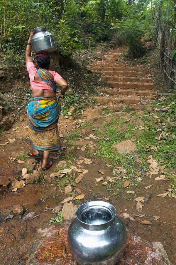 МАХАРАСТРА, ИНДИЯ, апрель 2013, женщина носит воду от потока стоковые изображения rf
