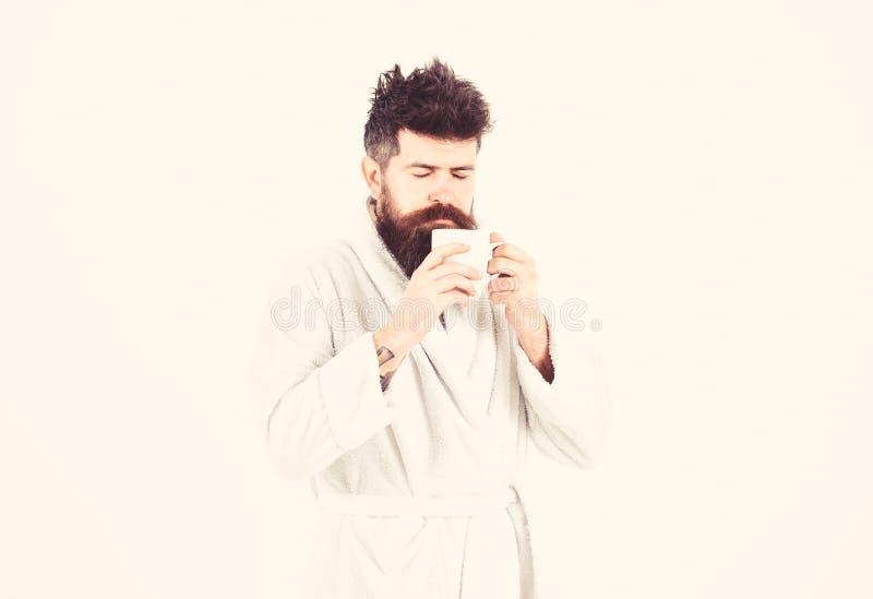 Мачо дремотная, сонная сторона выпивает кофе в утре наслаждаясь ароматностью Концепция ритуалов утра Человек с бородой и стоковая фотография rf