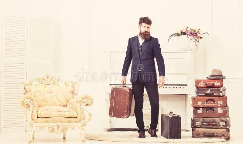 Мачо привлекательное, элегантный на строгой стороне носит винтажные чемоданы Человек с бородой и усик нося классический костюм стоковая фотография rf