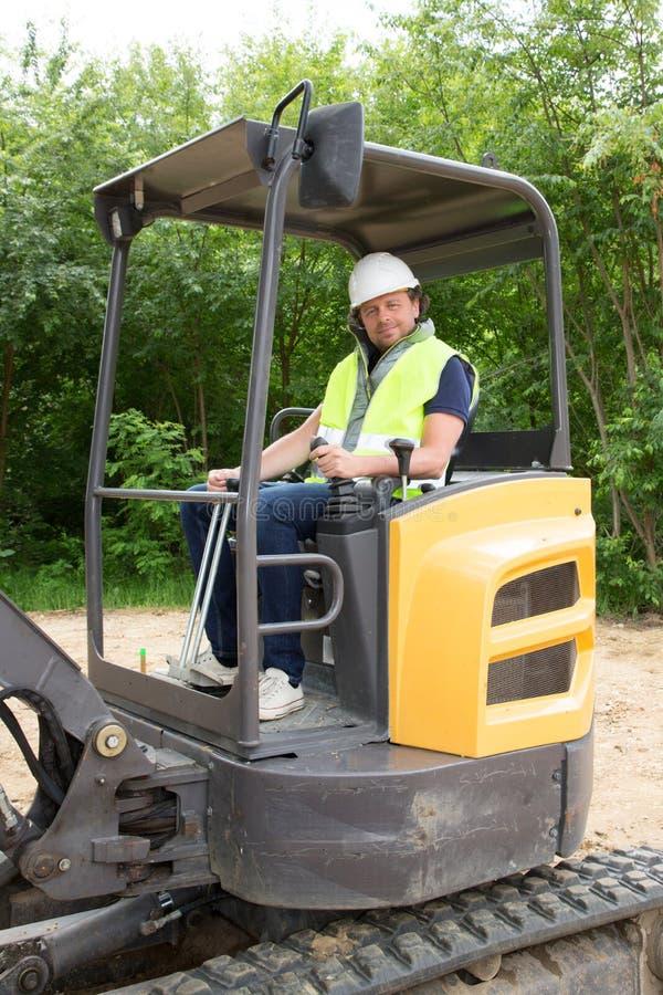 машина затяжелителя экскаватора водителя человека во время earthmoving работает outdoors на конструкции стоковое изображение