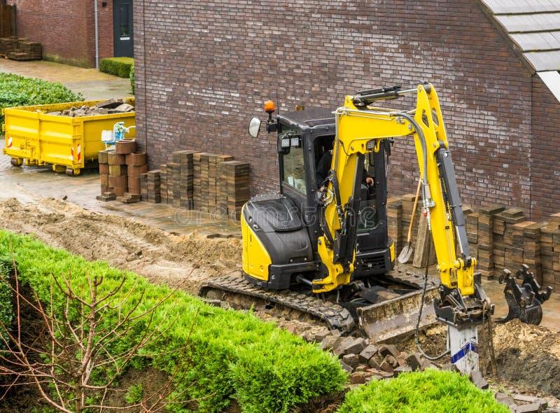 Машина землекопа работая на конструкции сада в современном районе стоковые изображения