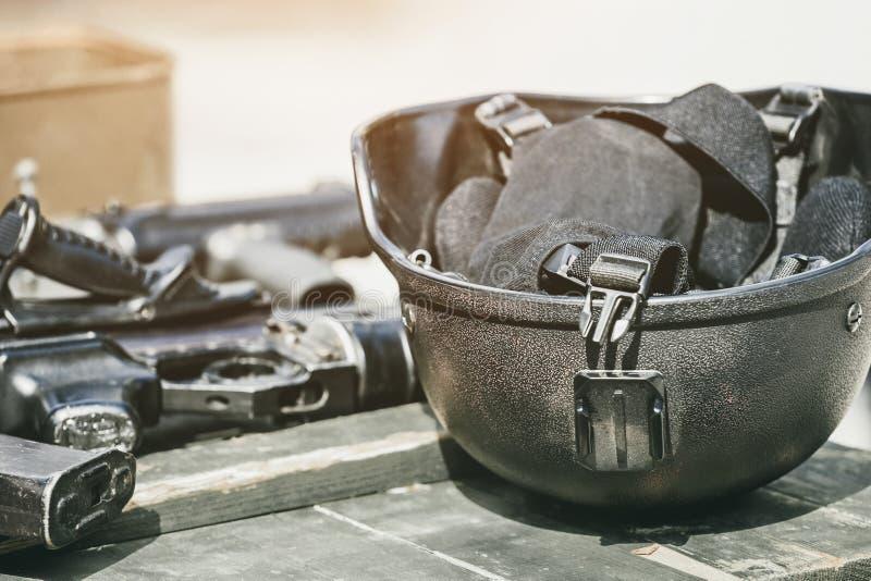 Машина, пулемет, шлем армии при электрофонарь лежа в куче на деревянной коробке боеприпасов стоковое фото rf