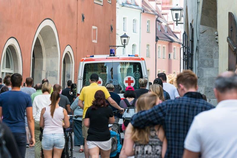 Машина скорой помощи с голубыми светами и толпой людей, Регенсбурга - Германии стоковое изображение