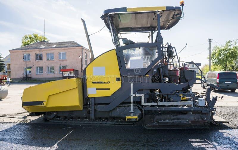 Машина paver асфальта работника работая во время строительства дорог и ремонтировать работает Фертиг-аппарат paver, фертиг-аппара стоковые фотографии rf