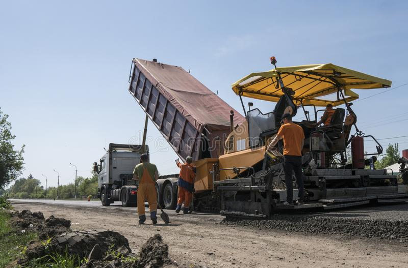 Машина paver асфальта работника работая во время строительства дорог и ремонтировать работает Фертиг-аппарат paver, фертиг-аппара стоковое изображение