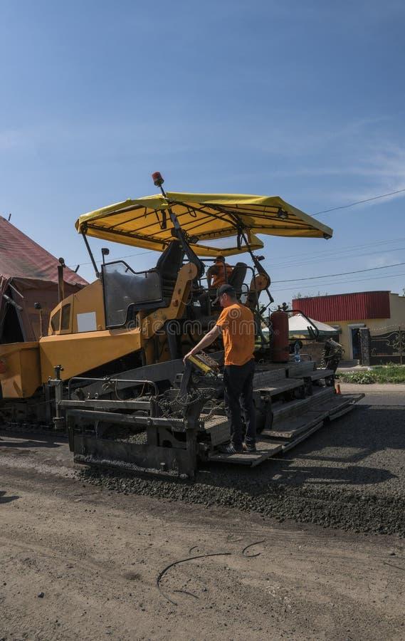 Машина paver асфальта работника работая во время строительства дорог и ремонтировать работает Фертиг-аппарат paver, фертиг-аппара стоковое изображение rf