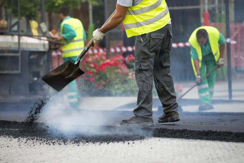 Машина paver асфальта работника работая во время строительства дорог стоковые фото