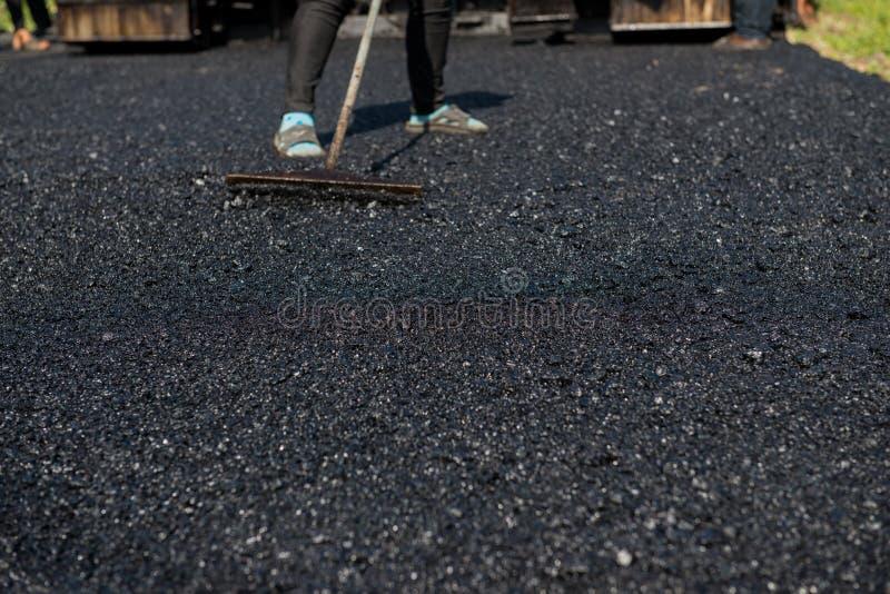 Машина paver асфальта работника работая во время строительства дорог стоковое фото