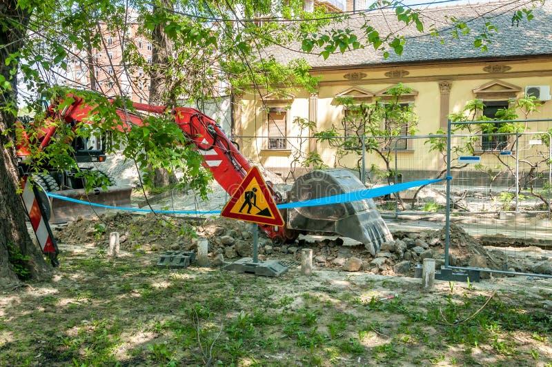 Машинное оборудование раскопк копает землю экскаватором от улицы в тени для новой линии кипятильной трубы района стоковое фото