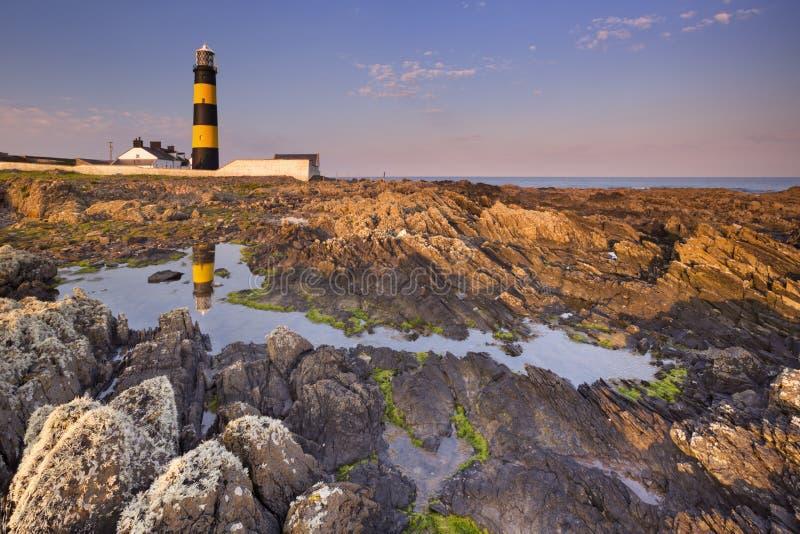 Маяк в Северной Ирландии на заходе солнца стоковое изображение