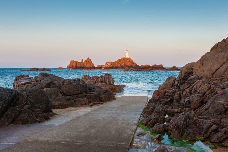 Маяк Джерси Corbiere Ла на восходе солнца и полной воде стоковые фото