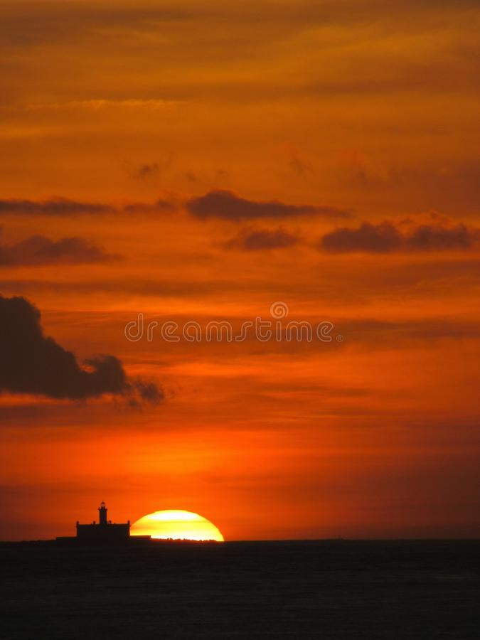 Маяк на заходе солнца: Глубокое оранжевое небо стоковая фотография rf