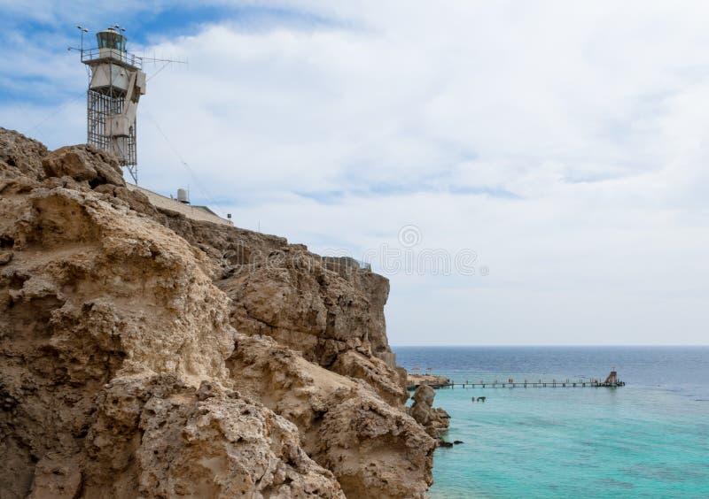 Маяк на каменном утесе на береге Красного Моря Египет на предпосылке голубого неба и облаков стоковые изображения