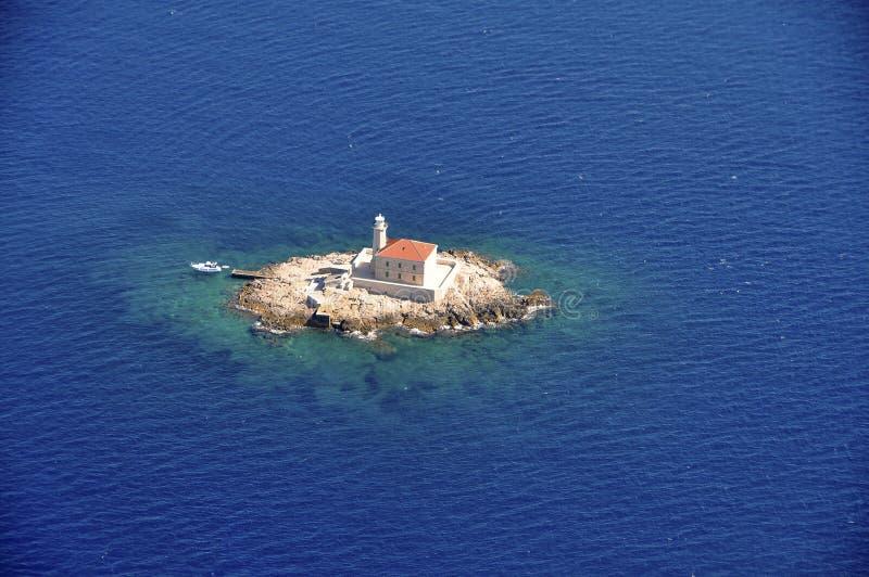 Download Маяк на малом утесе окруженном с морем сверху Стоковое Фото - изображение насчитывающей дел, навигация: 81813410
