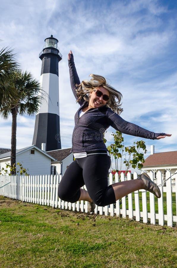Маяк острова Tybee в прибрежной Грузии Белокурая женщина скачет перед маяком стоковая фотография