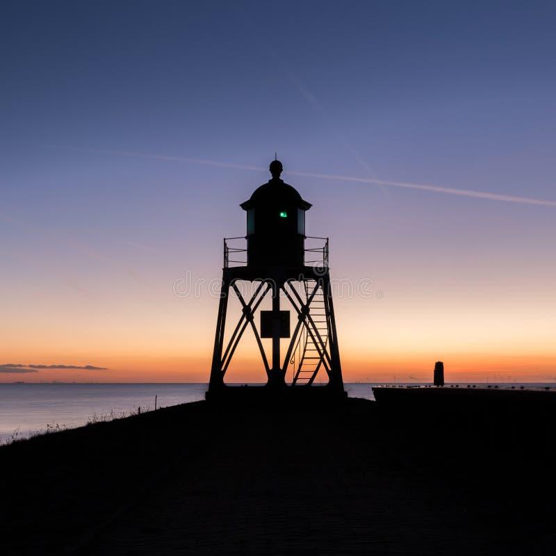Маяк с предпосылкой захода солнца стоковое фото rf