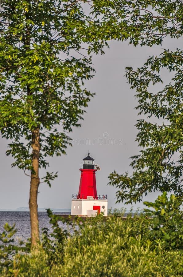 Маяк Pierhead Menominee обрамленный деревьями стоковое фото rf